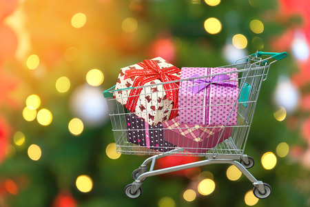 family mart: Christmas gifts and presents in shopping trolley cart with christmas tree and blurred lights background. Stock Photo