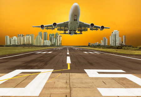 airplane flying take off from runway on sunset with modern skyscrapers background Stock Photo