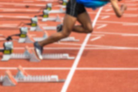 athlete leaving starting blocks for a sprint run on the running track
