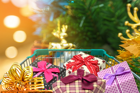 Christmas gifts and presents in shopping trolley cart with christmas tree background. Stock Photo