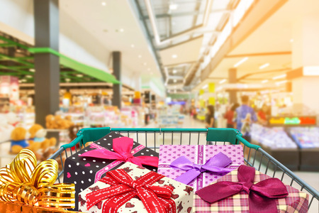 family mart: presents ribbon gift box in shopping trolley cart isolated on white background in shopping mall Stock Photo