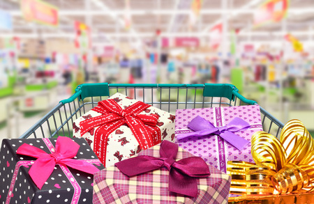 presents ribbon gift box in shopping trolley cart  in shopping mall Stock Photo