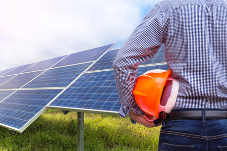 solar power station: engineer stand holding yellow construction helmet in solar power station