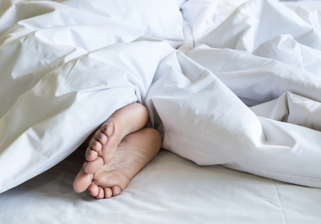 woman feet under white blanket and bed sheet
