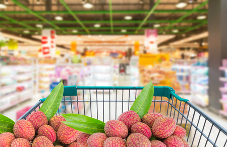 fresh ripe litchi fruits in shopping trolley cart in  supermarket