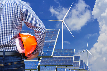 solar farm: engineer stand holding yellow construction helmet in solar farm and wind turbines generating electricity power station