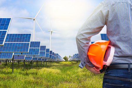 generating station: engineer stand holding yellow construction helmet in solar farm and wind turbines generating electricity power station