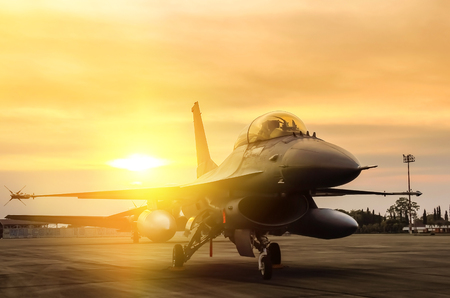 f16 falcon fighter jet military aircraft parked in airforce on sunset background