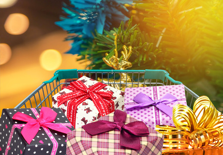 Christmas gifts and presents in shopping trolley cart with blurred lights background.