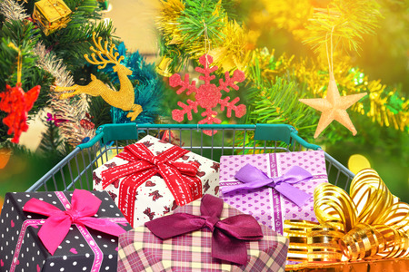 Christmas gifts and presents in shopping trolley cart with christmas tree decorations background.