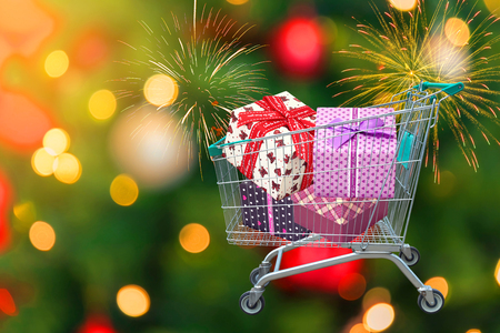 presents ribbon gift box in shopping trolley cart and blurred lights with firework background.