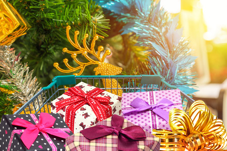 family mart: Christmas gifts and presents in shopping trolley cart with christmas tree decorations background.