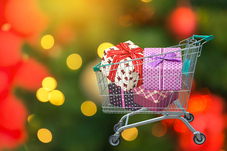 presents ribbon gift box in shopping trolley cart and blurred lights background.