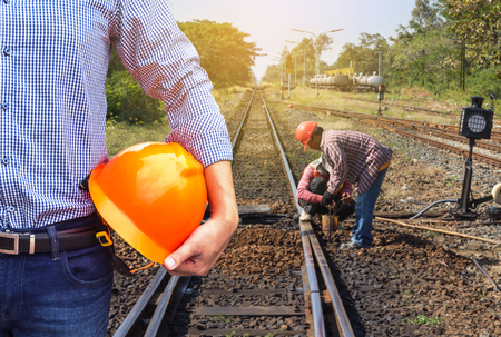 engineer holding yellow safety helmet with worker maintenance repairing change railway sleepers