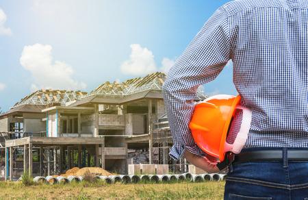 건설 현장에서 새로운 가정 건물에서 노란색 안전 헬멧을 들고 상주 엔지니어