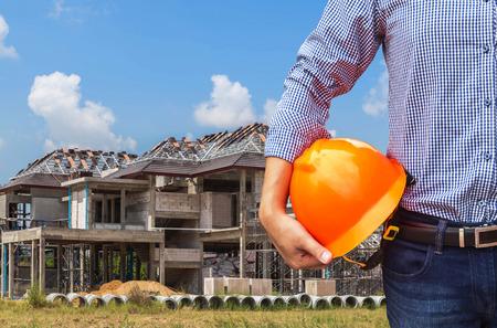 新しいホームの住宅開発の建設の背景に黄色の安全ヘルメットを保持しているエンジニア 写真素材