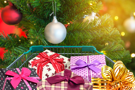 presents and christmas gifts in shopping trolley cart with christmas tree decorations background. Stock Photo