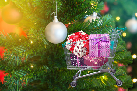 family mart: presents and christmas gifts in shopping trolley cart with christmas tree decorations background. Stock Photo