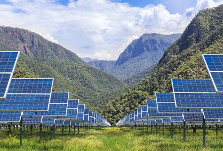 山の背景を持つ太陽光発電所に太陽光発電パネル 写真素材