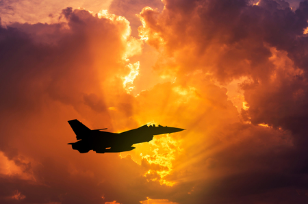 silhouette F - 16  falcon fighter jet military aircraft flying on sunset  background Standard-Bild
