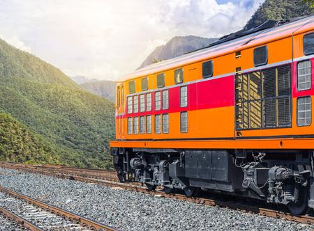 orange diesel engine locomotive passenger train crossing valley mountains