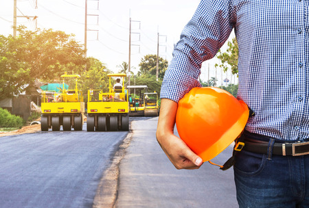 pneumatic tyres: engineer holding safety helmet at road construction site with roller compactor working asphalt road