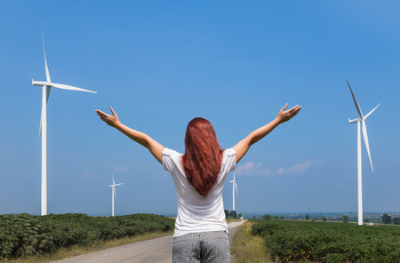 generating station: asian woman standing raised up arms achievements successful and celebrate in wind turbines generating electricity power station on blue sky background