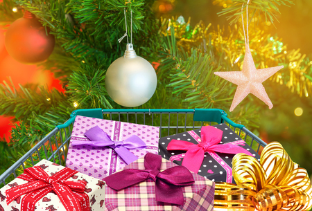presents  and christmas gifts in shopping trolley cart with christmas tree decorations background.