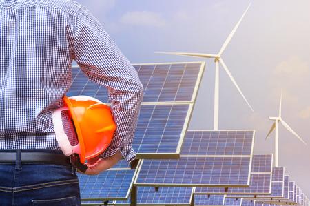 電力発電を生成する太陽光発電と風力発電タービンをフロント黄色安全ヘルメットを保持しているエンジニアのスタンド