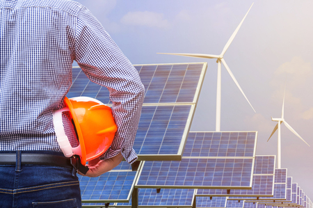 generating station: engineer stand holding yellow safety helmet front solar photovoltaic and wind turbines generating electricity power station