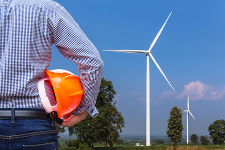 generating station: engineer stand holding yellow safety helmet with wind turbines generating electricity power station background