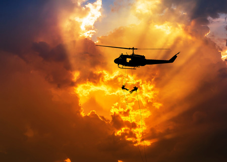 rappelling: silhouette soldiers in action rappelling climb down from helicopter with military mission counter terrorism assault training on sunset background