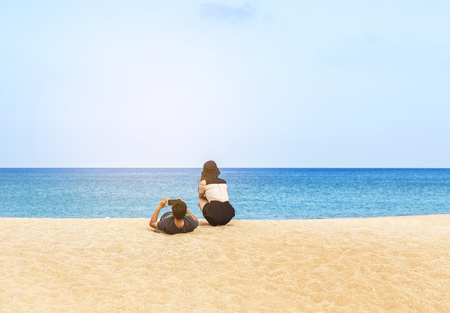 rear view young couple relaxing on the tropical beach and blue sky background