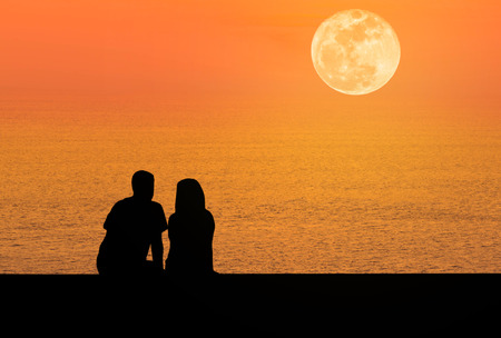 Romantic rear view of couple love sit relax on the tropical beach in sunset with full moon