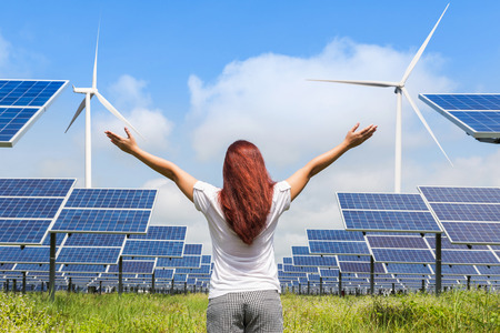 asian woman standing raised up arms achievements successful and celebrate front solar photovoltaic and wind turbines generating electricity power station Stock Photo