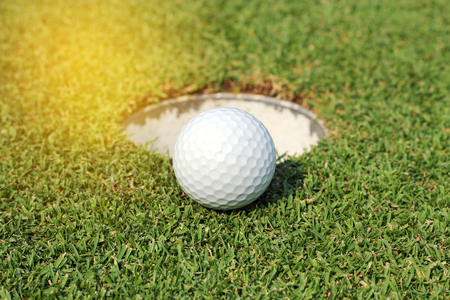 range of motion: golf ball near the hole on green grass Stock Photo