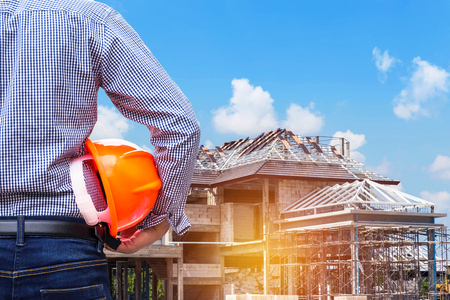 常駐技術者の工事現場の下で新しい家の建物に黄色い安全ヘルメットを保持