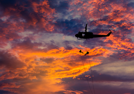 counter terrorism: silhouette soldiers in action rappelling climb down from helicopter with military mission counter terrorism assault training on sunset background