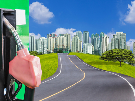 fuel nozzle service station with empty asphalt road with tree and modern city Stock Photo