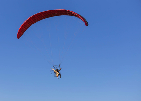 paraglider flying with paramotor on  blue sky  background