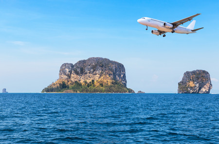 passenger airplane landing above small island in blue sea and tropical beach on blue sky  travel destinations concept.