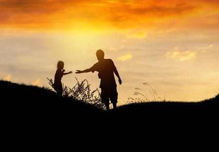 Silhouette father stretch hand helping to daughter on sunset Standard-Bild