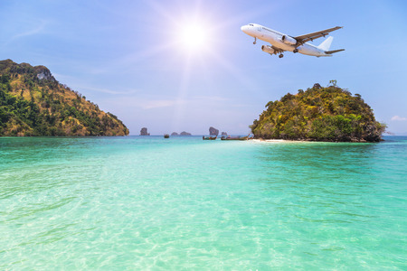 passenger airplane landing above small island in blue sea and tropical beach on blue sky with sunlight. travel destinations concept.