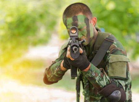 soldier face with jungle camouflage paint aiming automatic assault rifle selective focus