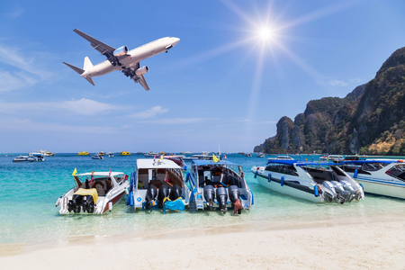 speedboats moored in the tropical sea with airplane landing above on blue sky with sunlight Stock Photo