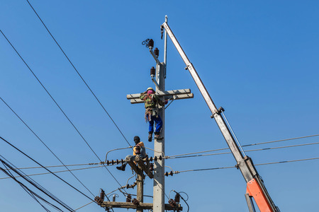 Electricians climbing work on electric power pole with crane on blue sky background