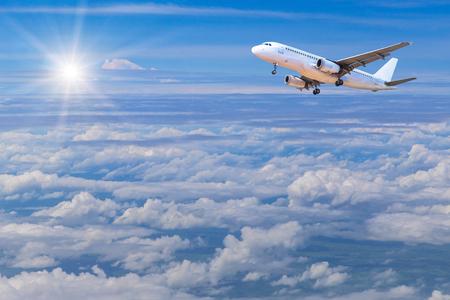 空太陽と白い雲の上の高度で飛んで飛行機