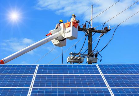 Elektrycy naprawy drutu linii energetycznej na wiadro hydrauliczne platformy podnoszenia z fotowoltaicznej w elektrowni słonecznej na błękitne niebo z promieni słonecznych Publikacyjne