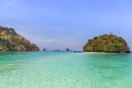 view of small island with longtail boat  in andaman sea with blue sky at krabi Thailand