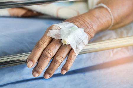 病棟病室で横になっている時に手に静脈内カテーテル注入プラグの高齢者患者の手を閉じる